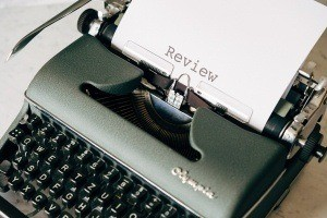 A typewriter with a book review being typed on a piece of paper.